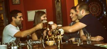 Vänner som har drinkar i en stång royaltyfri fotografi