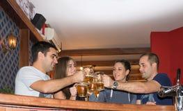 Vänner som har drinkar i en stång royaltyfri foto