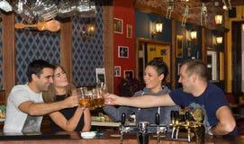 Vänner som har drinkar i en stång royaltyfria bilder
