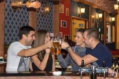 Vänner som har drinkar i en stång arkivbilder