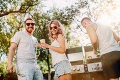 Vänner som har ett grillfestgallerparti med utomhus- drinkar, mat och att laga mat i trädgård arkivfoto