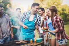 Vänner som har ett grillfestparti i natur Royaltyfri Bild