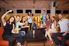 Vänner som har fritid i bowlingklubba Arkivfoto
