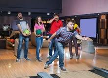Vänner som har gyckel i bowling Arkivbilder