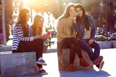 Vänner som har gyckel med smartphones Royaltyfri Foto