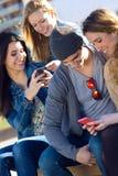 Vänner som har gyckel med smartphones Arkivfoton
