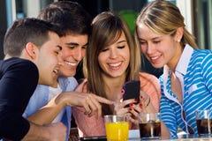 Vänner som har gyckel med smartphones Arkivfoto