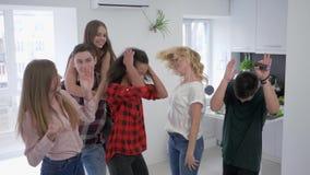 Vänner som har gyckel och dansar i kök, smällare för vredesutbrott för ung man färgrik med en konfetti i ultrarapid på ett lager videofilmer