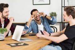 Vänner som har gyckel på mötet, medan ett sätter bitcoins royaltyfri foto