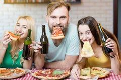 Vänner som har pizzapartiet hemma Arkivfoto