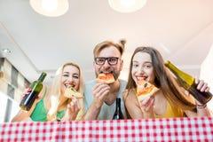 Vänner som har pizzapartiet hemma Royaltyfria Foton