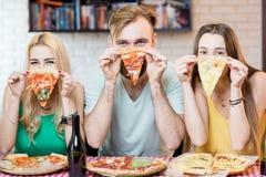 Vänner som har pizzapartiet hemma Royaltyfri Fotografi