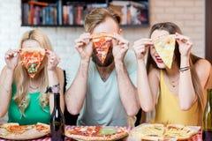 Vänner som har pizzapartiet hemma Arkivfoton