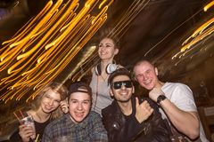Vänner som har roligt och dricker öl i nattklubb exponering long royaltyfria bilder