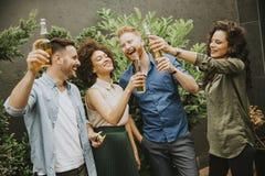 Vänner som har utomhus- rostat bröd för trädgårds- parti med alkoholiserad äppeljuice D royaltyfria foton