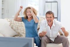 Vänner som hemma håller ögonen på tv:n i vardagsrumet Royaltyfri Bild