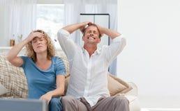 Vänner som hemma håller ögonen på tv:n i vardagsrumet Fotografering för Bildbyråer