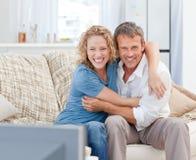 Vänner som hemma håller ögonen på tv:n i vardagsrumet Arkivfoton