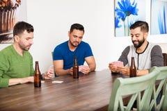 Vänner som hemma spelar poker arkivbilder