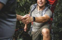 Vänner som hjälper att klättra i skog arkivbild