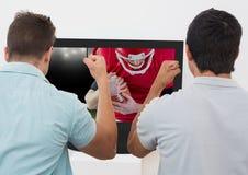Vänner som hurrar, medan hålla ögonen på den amerikanska fotbollsmatchen på television Arkivbilder