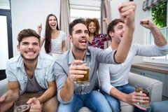 Vänner som hurrar, medan hålla ögonen på fotbollsmatchen på TV royaltyfria foton