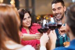 Vänner som klirrar exponeringsglas av vin på restaurangen royaltyfri foto