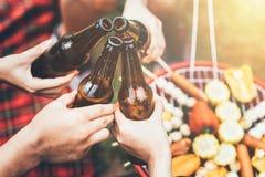 Vänner som klirrar flaskan av öl under det campa partiet Arkivbild