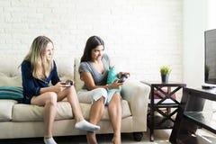 Vänner som konkurrerar, medan spela videogamen hemma royaltyfri foto
