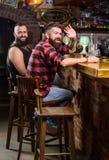Vänner som kopplar av i bar Beställningsdrinkar på stångräknaren Brutal skäggig man för Hipster att spendera fritid med vännen på arkivbilder