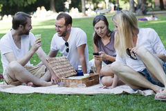 Vänner som kopplar av i park Royaltyfria Foton