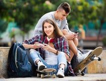 Vänner som kopplar av med mobiltelefoner Arkivfoton