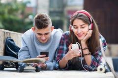 Vänner som kopplar av med mobiltelefoner Arkivbild
