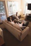 Vänner som kopplar av, medan ha kaffe i vardagsrummet royaltyfri fotografi