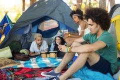 Vänner som kopplar av på campingplatsen fotografering för bildbyråer