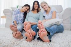 Vänner som kopplar av på golv och ler på kameran royaltyfri fotografi