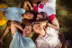 Vänner som kopplar av på gräs parkerar in arkivfoto