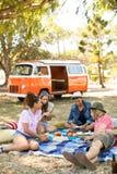 Vänner som kopplar av på picknickfilten på fältet arkivbilder