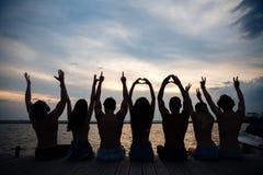 Vänner som kopplar av på sjösidan arkivfoto