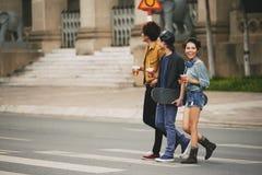 Vänner som korsar gatan i centrum Arkivbild