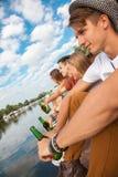 Vänner som kyler nära sjön Fotografering för Bildbyråer