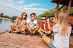 Vänner som kyler nära sjön Arkivbild