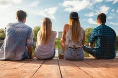 Vänner som kyler nära sjön Royaltyfri Foto