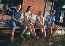 Vänner som kyler nära sjön Arkivbilder