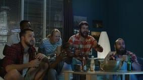Vänner som kyler på soffan, medan hålla ögonen på leken på TV arkivfilmer