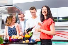 Vänner som lagar mat pasta i inhemskt kök Royaltyfri Fotografi