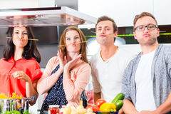 Vänner som lagar mat pasta och kött i inhemskt kök Fotografering för Bildbyråer