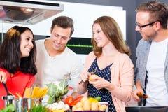 Vänner som lagar mat pasta och kött i inhemskt kök Royaltyfri Bild
