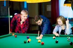 Vänner som leker billiard Arkivbild