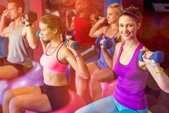 Vänner som lyfter vikter i idrottshall Royaltyfri Bild